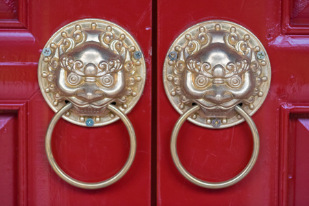 Golden colored chinese door knockers on a red door in China