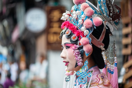 Chongqing, China - June 13, 2018 : Woman with chinese opera traditional dress and make-up in CiQiKou touristic street