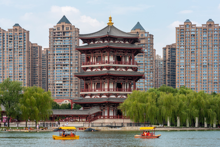 Xian, Shannxi province, China - Aug 12, 2018 : Boats with tourists on a lake with pagoda against buildings in Tang paradise park.
