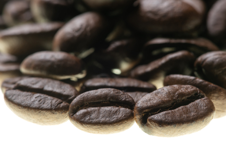 Heap of roasted coffee beans backlit on white close-up view