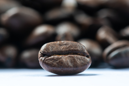Roasted coffee bean with heap of beans in the background