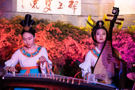 Chengdu, Sichuan province, China - Feb 5, 2019 : Chinese female musicians and dancers performing a public show at night at HeJiang pavilion Éditoriale