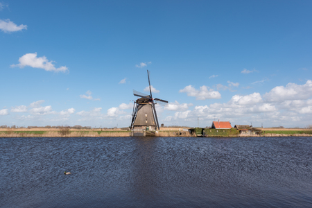 Kinderdijk, Netherlands - March 23, 2016 : Landscape with a windmill against blue sky and white clouds