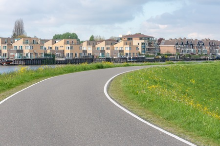 Empty curved road on a dam in the dutch countryside, Capelle Aan Den Ijssel, Netherlands 免版税图像