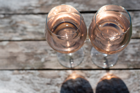 Two glasses of rose wine on a wooden table in sunlight top view