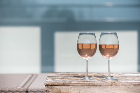 Two glasses of rose wine on a wooden table in sunlight