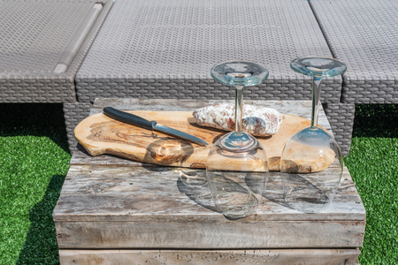 Two empty wine glasses and a dried sausage with a knife on a wooden table in a garden on a sunny day