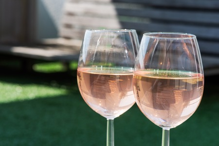 Two glasses of rose wine on a wooden table under sunlight  with a garden bench in the background