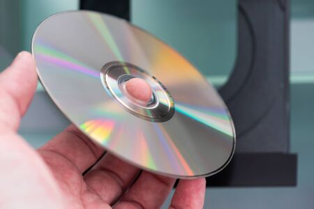 Hand holding a CD above a CD player, close-up Archivio Fotografico