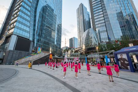 Chengdu, Sichuan province, China - June 6, 2019 : Senior women with red outfit practicing  dancing in front of Evergrande plaza commercial mall Éditoriale