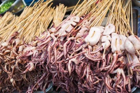 Squid skewers heap in a street market in Luodai, Chengdu, Sichuan province, China