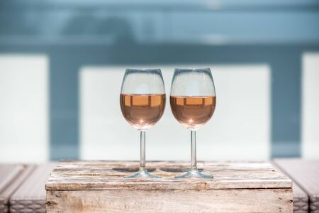 Two rose wine glasses on a small wooden table in springtime