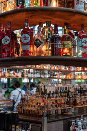 Paris, France - April 15, 2019 : Large collection of alcohol bottles on shelves in La Felicita Bar-Restaurant in the 13th arrondissement of Paris