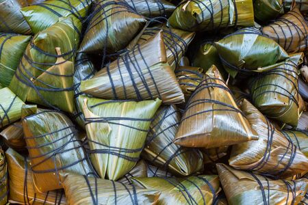 Heap of ZhongZi - traditional Chinese rice dish made of glutinous rice stuffed and wrapped in bamboo leaves in a street market, Chengdu, Sichuan province, China Stock Photo