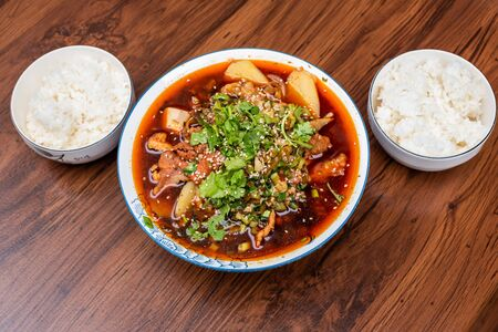 Maocai Sichuan food dish in a bowl and rice on a table Stock Photo