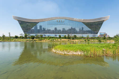 Chengdu, Sichuan province, China - Aug 26, 2020 : New Century Global Center building reflecting in a lake on a sunny day with clear blue sky 新闻类图片