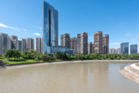 Chengdu, Sichuan province, China - Aug 24, 2020 : Minyoun central hotel and residential buildings along the jinJiang river in Wuhou district on a sunny day