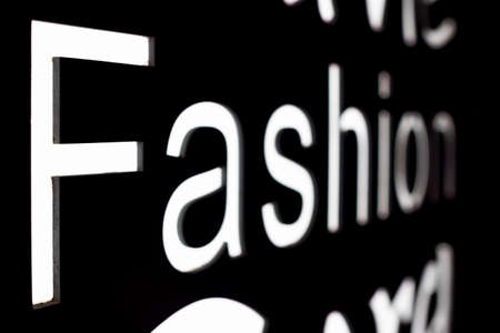Fashion word in illuminated letter on a black background close-up view