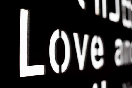 Love word in illuminated letter on a black background close-up view 免版税图像
