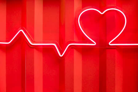 Red neon heart shape and heartbeat line on metal wall close-up view 免版税图像