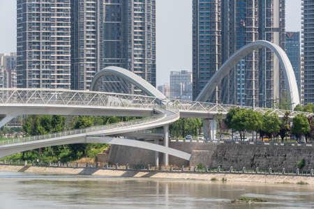 Chengdu, Sichuan province, China - July 2, 2020: Wuchazi and HongXingLu KuaJinJiangQiao bridges also called butterfly bridge against skyscrapers panorama in daylight 新闻类图片