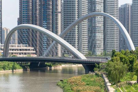 Chengdu, Sichuan province, China - July 2, 2020: HongXingLu KuaJinJiangQiao bridge also called butterfly bridge against skyscrapers panorama in daylight