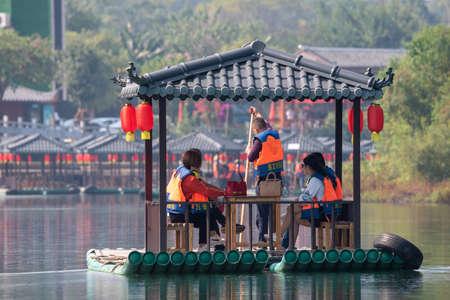 Yangshuo, Guilin, Guangxi province, China - November 10, 2019: Tourists on a bamboo raft with chinese lanterns on Li river.