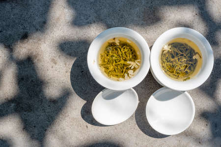 Two white cups of tea top view on a grey stone table in sunlight under a tree in Chengdu, Sichuan province, China