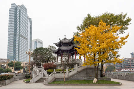 Chengdu, Sichuan province, China - December 7, 2019 : HeJiang chinese pavillion and gingko tree with yellow leaves in autumn.