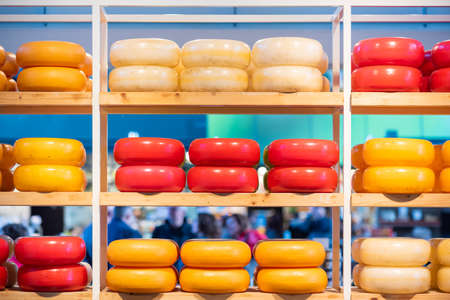 Yellow and red gouda wheels stacks on a market stall in Rotterdam, South Holland, Netherlands