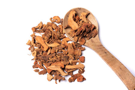 Lesser galangal, latin name Alpinia officinarum dried roots heap wth a wooden spoon close-up view on white background