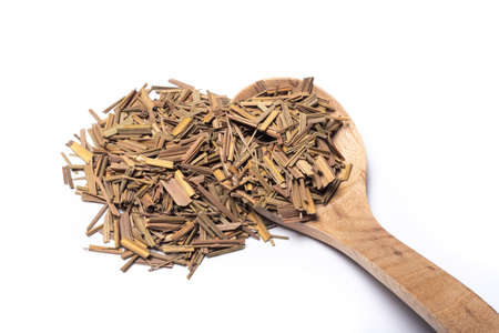 Organic dried lemongrass, latin name cymbopogon citratus heap with a wooden spoon on white background