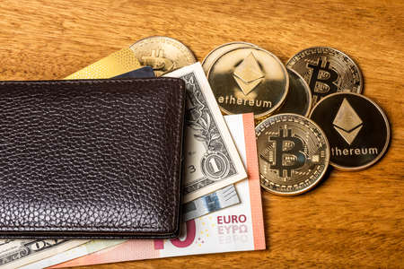 Financial concept with physical bitcoin and ethereum and a wallet with Euro, Dollar bills and credit cards. Banque d'images