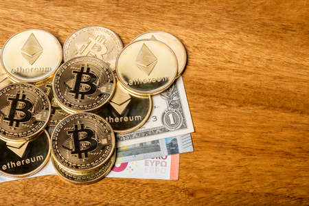 Financial concept with physical bitcoin and ethereum and Euro, Dollar bills on a wooden table Banque d'images
