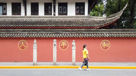 Chengdu , Sichuan province, China - July 28, 2020 : woman walking in the street with Wenshu monastery surrounding red wall in the background Éditoriale