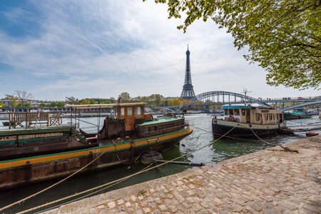 Paris, France - April 15, 2019 : Seine river banks with boats with the Eiffel tower in the background Éditoriale