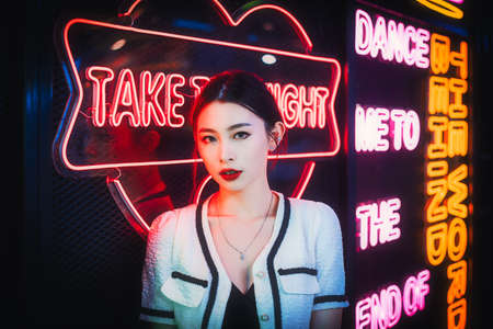 Young chinese woman standing next to neon lights in Chengdu, Sichuan province, China Banque d'images