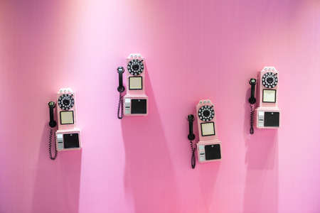 Four old vintage phones hanging on a pink wall background