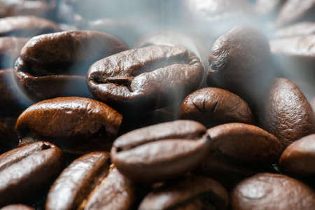 Heap of roasted coffee beans close-up view with smoke Banque d'images
