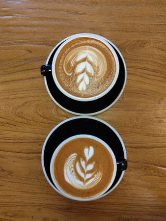 Two cups of cappuccino on a wooden table top vertical view