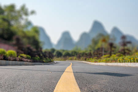 Empty road and limestone karst hills landscape with tilt-shift focus effect in Yangshuo, Guangxi province, China
