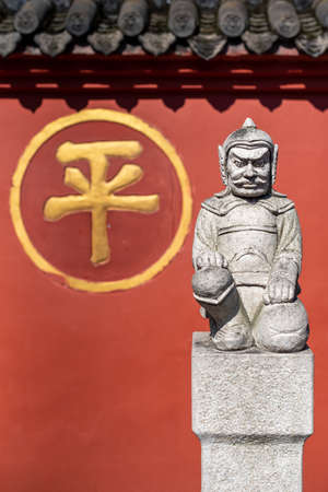 Chengdu, Sichuan province, China - Sept 28, 2021 : Soldier sculpture in front of the red surrounding wall of Wenshu buddhist monastery with the chinese character - ping- meaning peace. Éditoriale