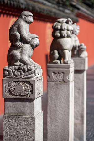Chengdu, Sichuan province, China - Sept 28, 2021 : Three statues in front of the red surrounding wall of Wenshu buddhist monastery.