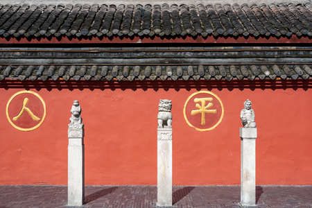Chengdu, Sichuan province, China - Sept 28, 2021 : Three statues in front of the red surrounding wall of Wenshu buddhist monastery with the chinese characters - ren ping- meaning people peace.