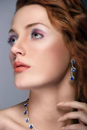 closeup woman beautiful redhead face with blue jewelry photo