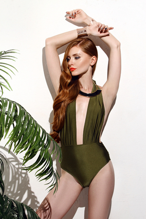 Sexy girl with red hair standing on isolated white background in green bikini swimsuit With palm branches, stylish and accessories, looks expensive and luxery, perfect for photo advertising, vogue style Stock Photo