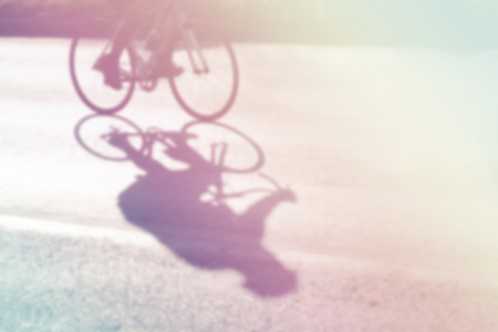 Abstract motion blur uette of cyclist on the street at sunrise, fill color filter pastel gradient tone.