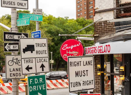 Many signs at a street corner in New York City