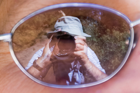 mirror image: Mirror image of a photographer taking a picture of a Monarch butterfly on his own hat, using the reflection in the lens a womans glasses