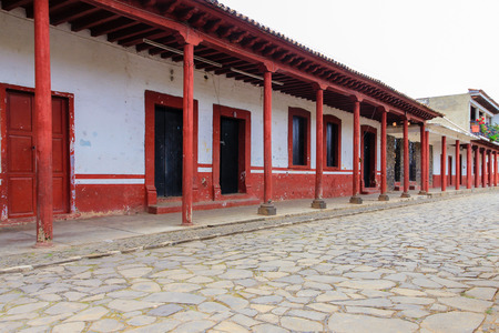 dominant color: An empty plaza with a row of colorful columns in Tzintzuntzan, Michoacan, Mexico